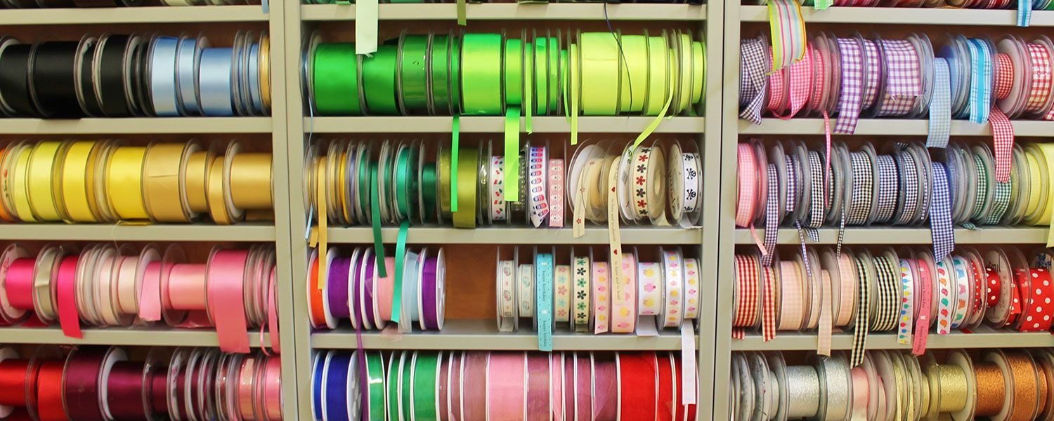 Fabrics, haberdashery, knitting and sewing shops insurance: A shelf featuring rolls of ribbons.
