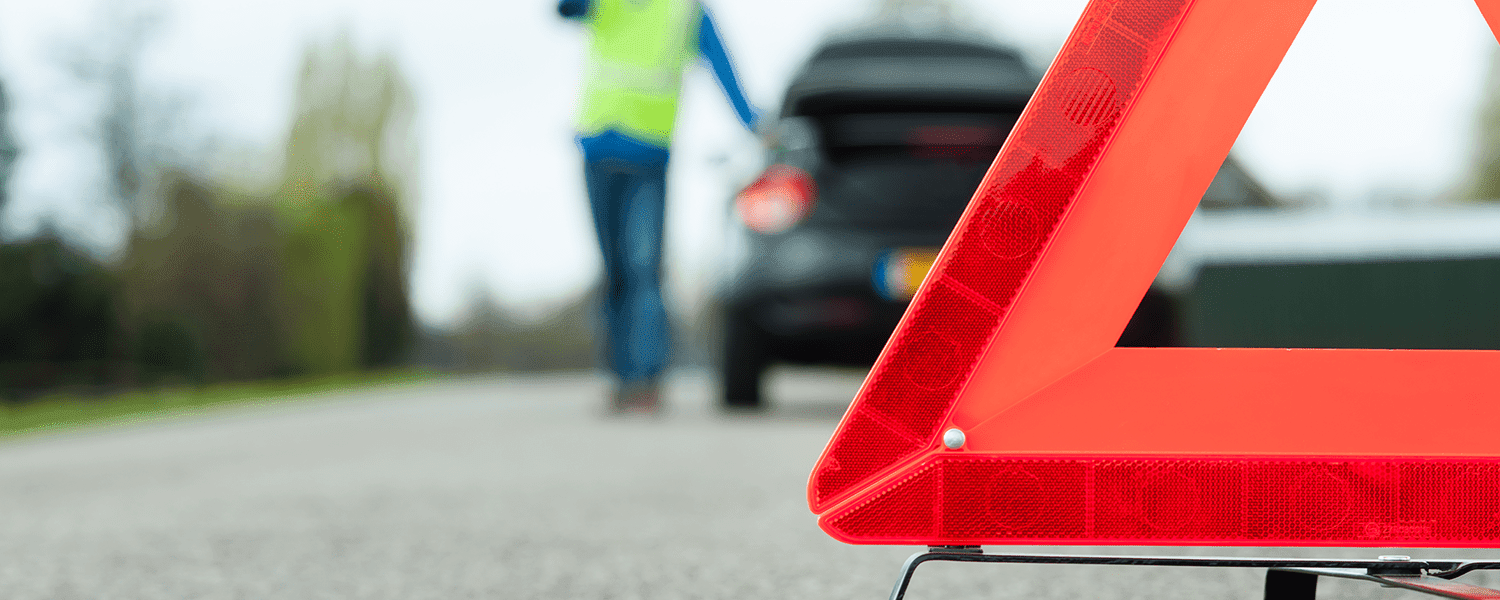 Breakdown insurance: Red triangle warning propped up near a person standing outside of their car.