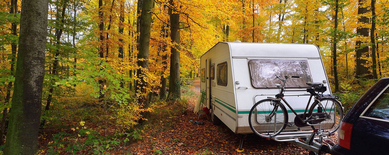 Caravan insurance: A caravan sitting in the woods attahced to a car with a bike holder.