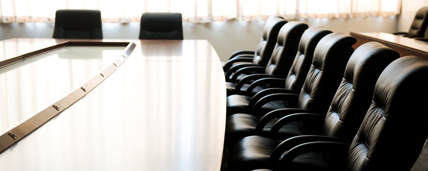 Directors and Officers: Empty row of black chairs at a conference table.