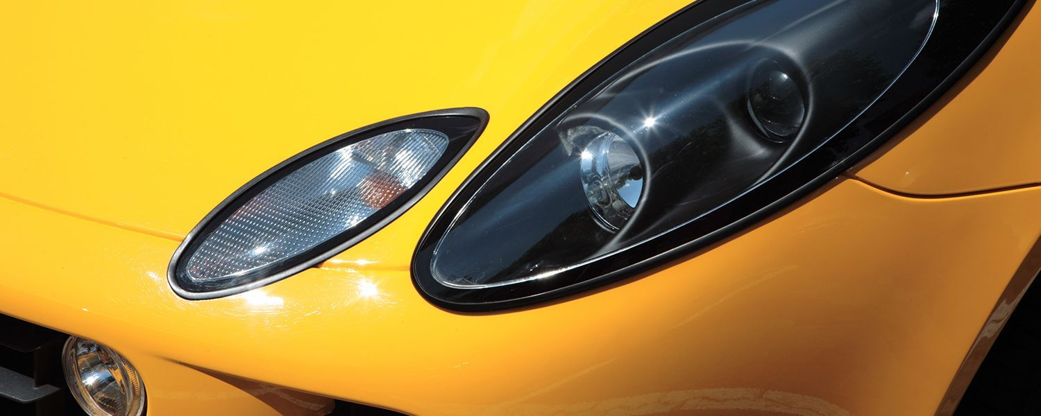 Lotus scheme: Close-up on the headlight of a yellow lotus car.