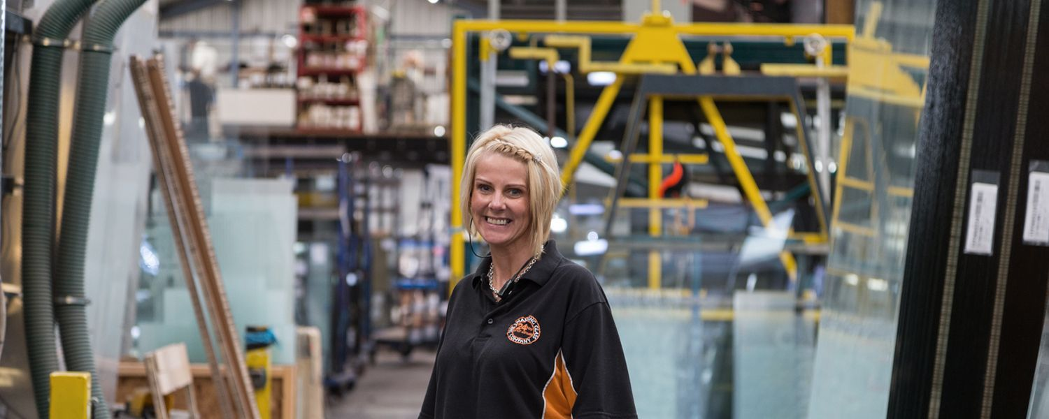 Manufacturers insurance: A smiling woman standing inside a warehouse.
