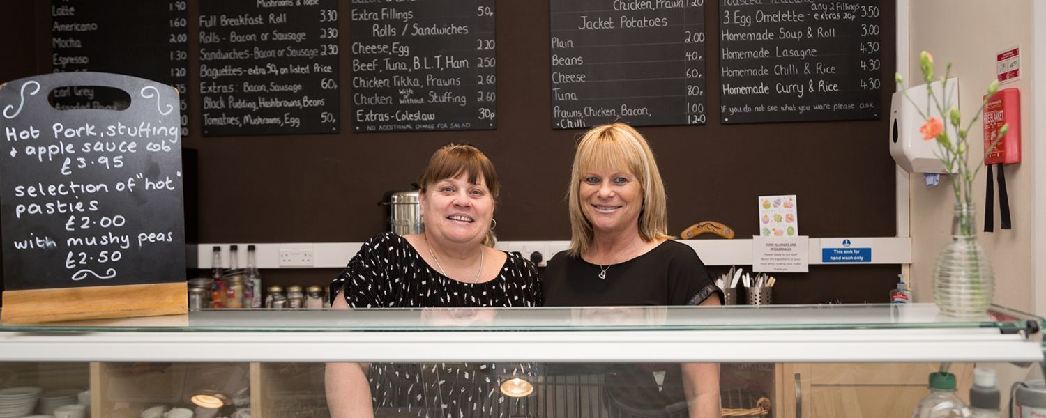Retailers insurance: Two smiling women standing together behind a cafe counter.