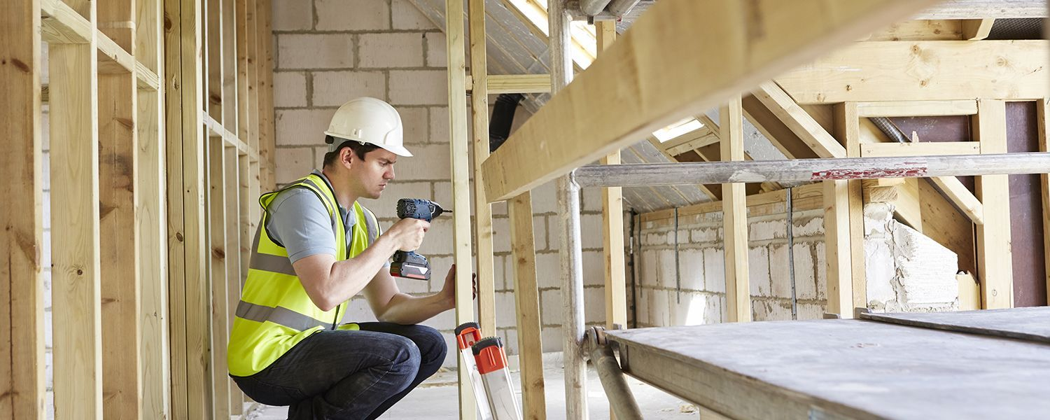 Tradespeople insurance: A male builder using a drill on some wooden planks.