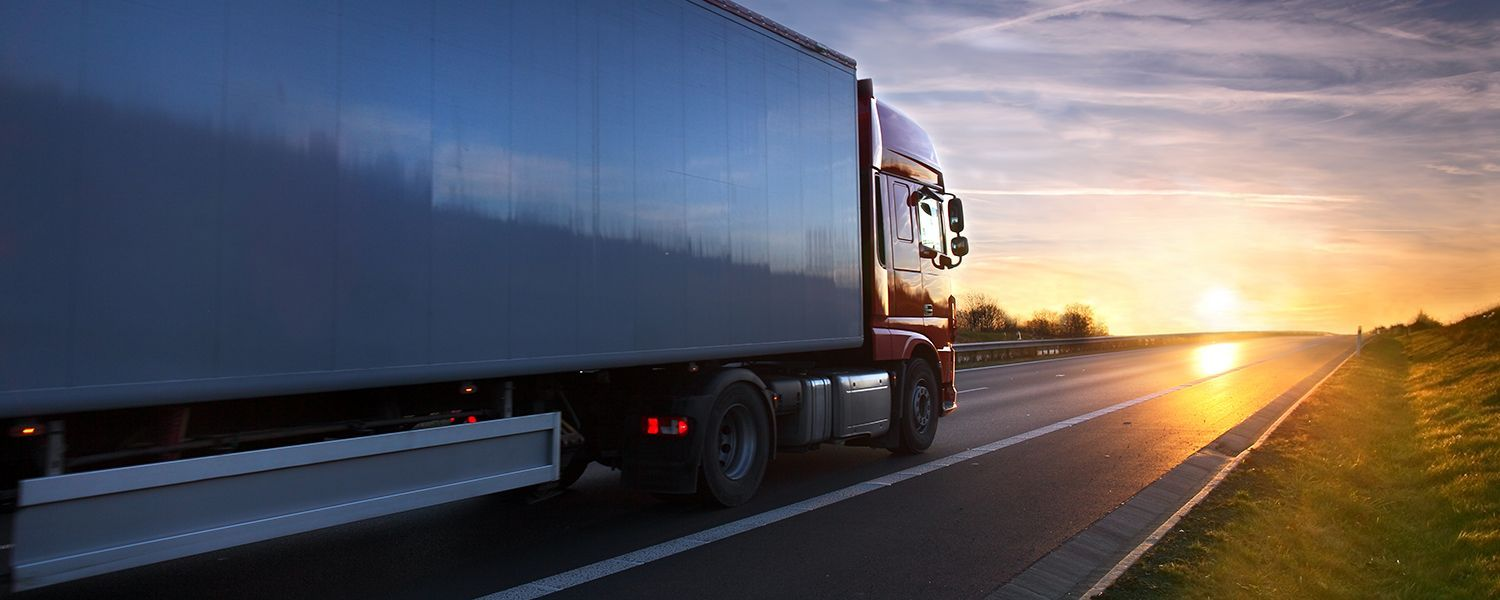 Transportation vehicles: A large truck driving on a road to deliver goods.