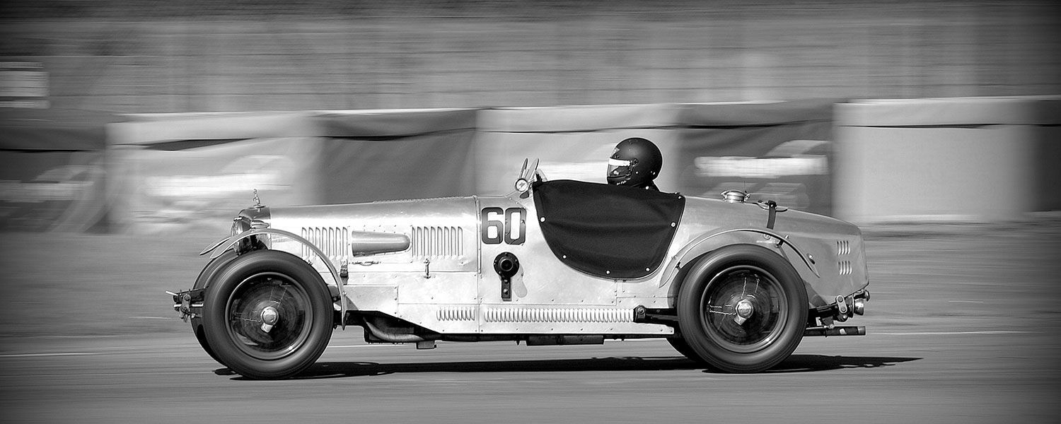 Vintage sports car club: A helmeted person driving a vintage sports car with the number 60 on it.