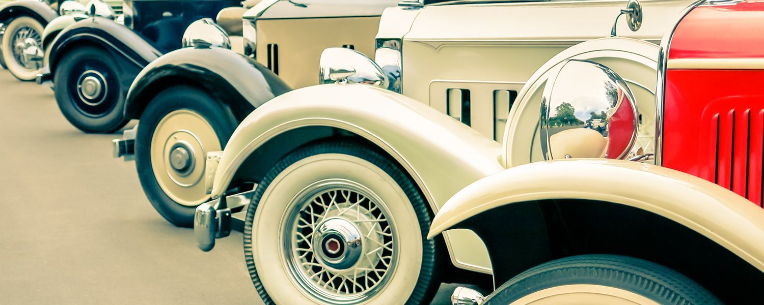Vintage vehicles: Close-up of a row of vintage car's wheels.