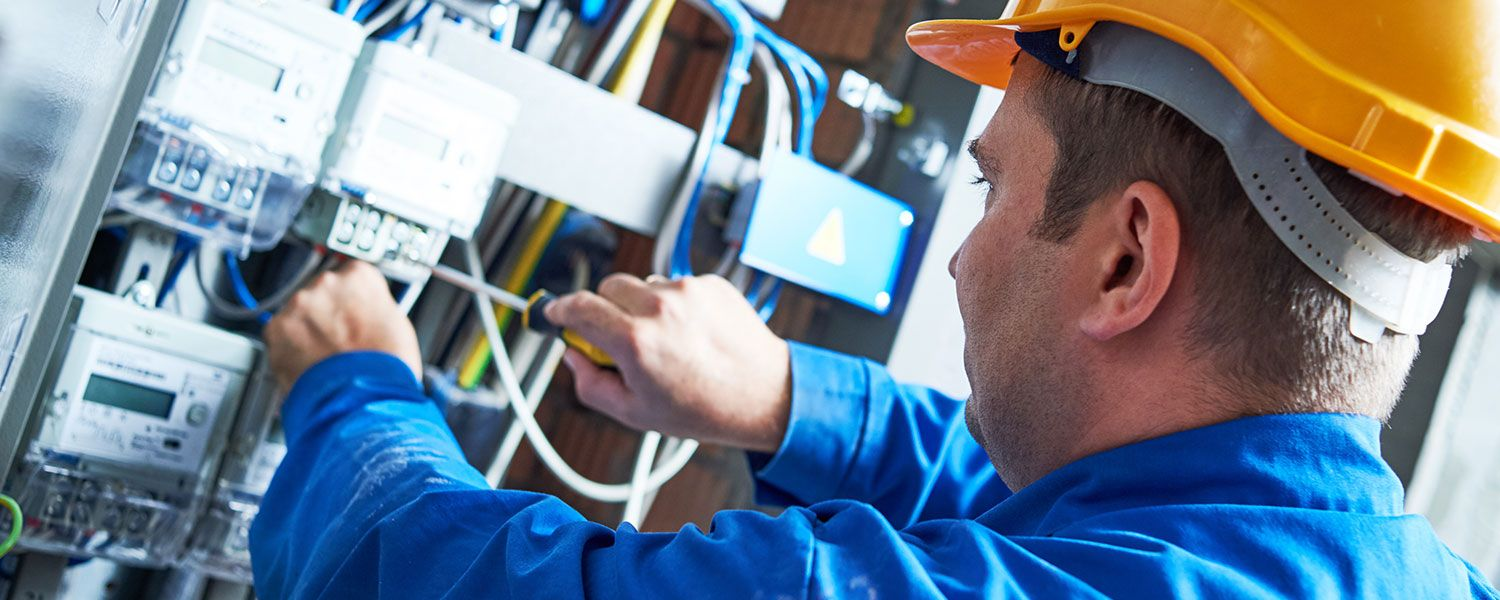 Electricians insurance: An electrician working within a fuse box.